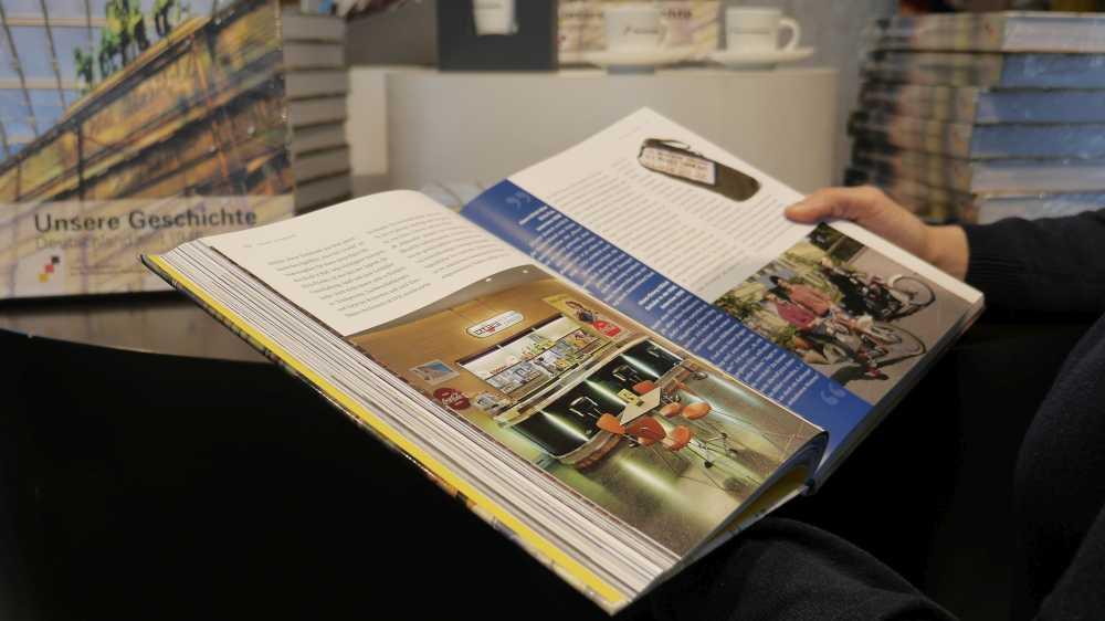 Ein aufgeschlagenes Begleitbuch zur Ausstellung Unsere Geschichte. Deutschland seit 1945 mit weiteren Exemplaren im Hintergrund