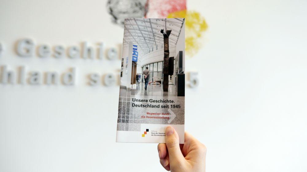 Eine Hand hält das Wegweiser-Heft vor der Dauerausstellung