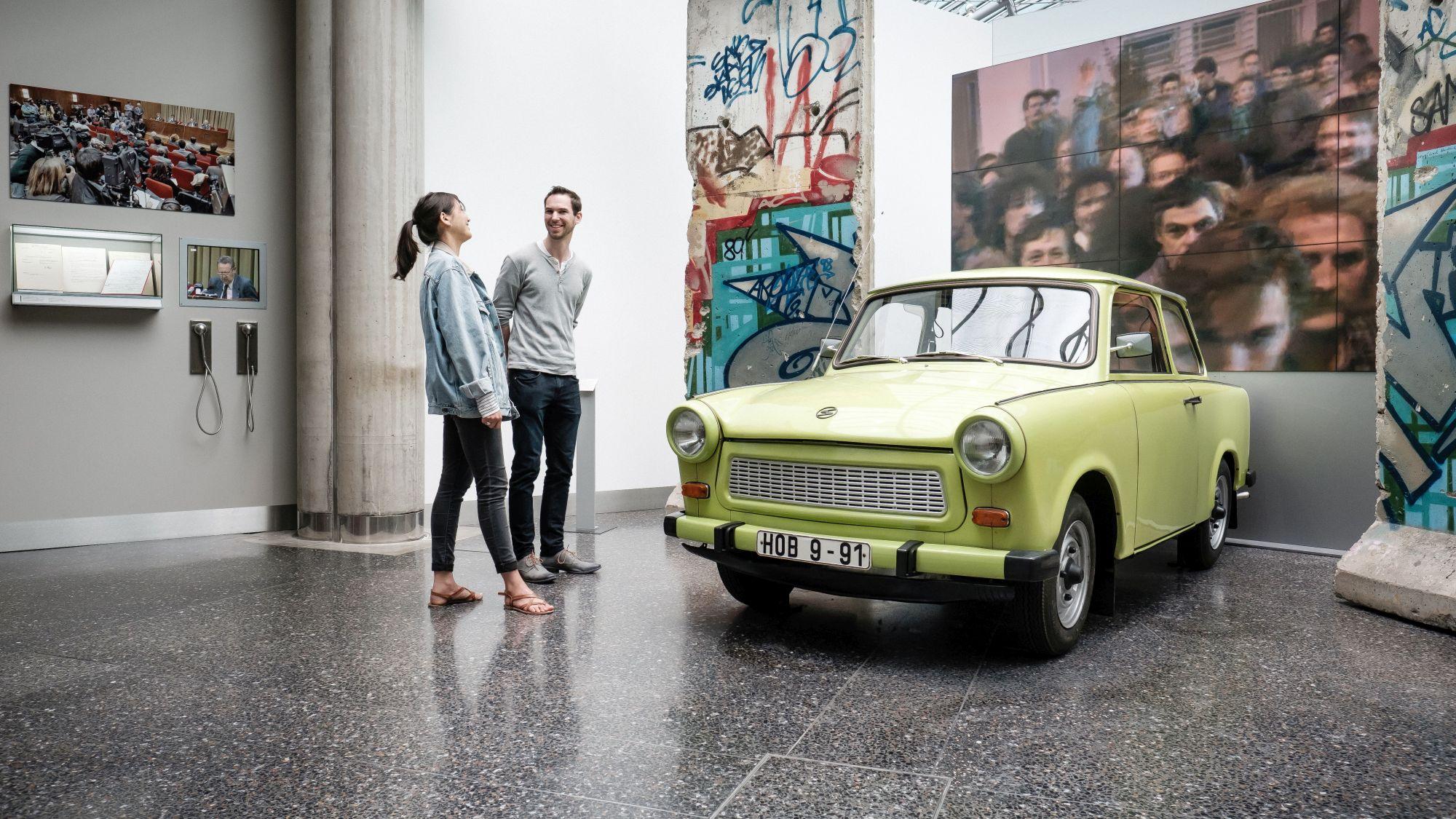 Eine junge Frau und ein junger Mann unterhalten sich in der Ausstellung neben einem grünen Trabi, der zwischen zwei großen Mauerteilen der Berliner Mauer steht.