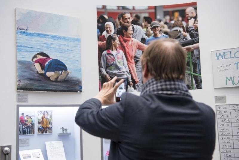 Besucher fotografiert Ausstellung mit dem Smartphone.