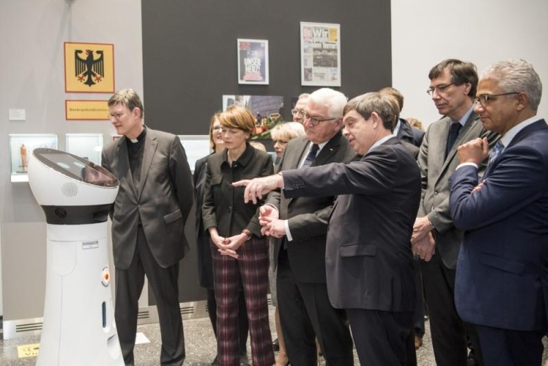 Frank-Walter Steinmeier und seine Begleiter mit Service-Roboter.