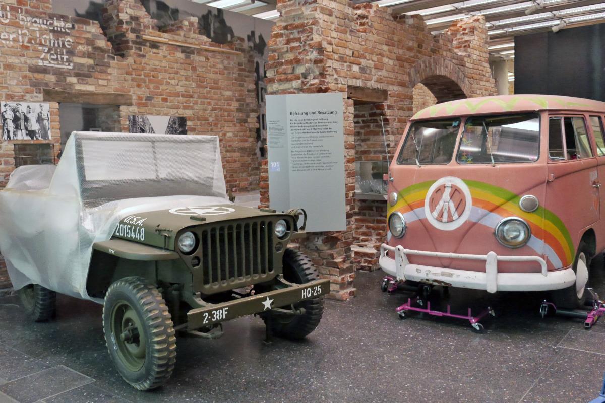 Ein Militärjeep und ein VW-Bulli nebeneinander geparkt.