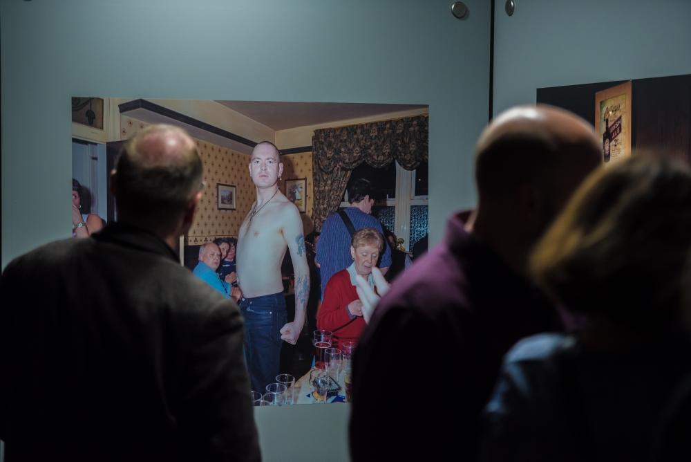 Besucherinnen und Besucher vor einer Fotografie von Peter Dench.