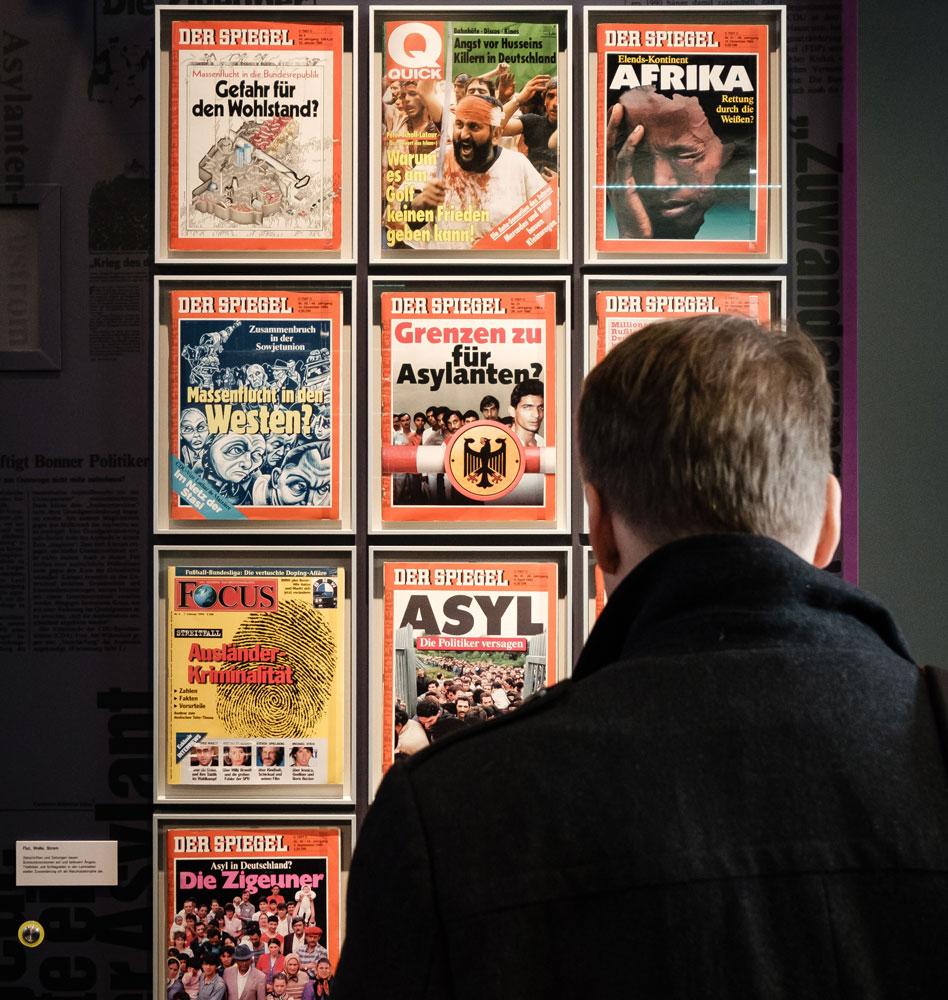 Ein Besucher betrachtet Magazin-Cover der 1990er Jahre.
