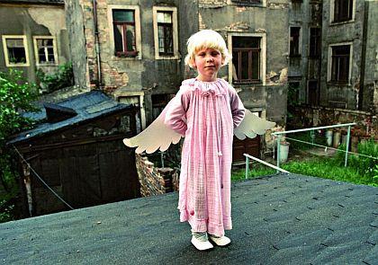Das Foto zeigt ein kleines Mädchen in einem Altbau-Hinterhof, verkleidet als Engel in rosa Kostüm mit herunterhängenden Flügeln