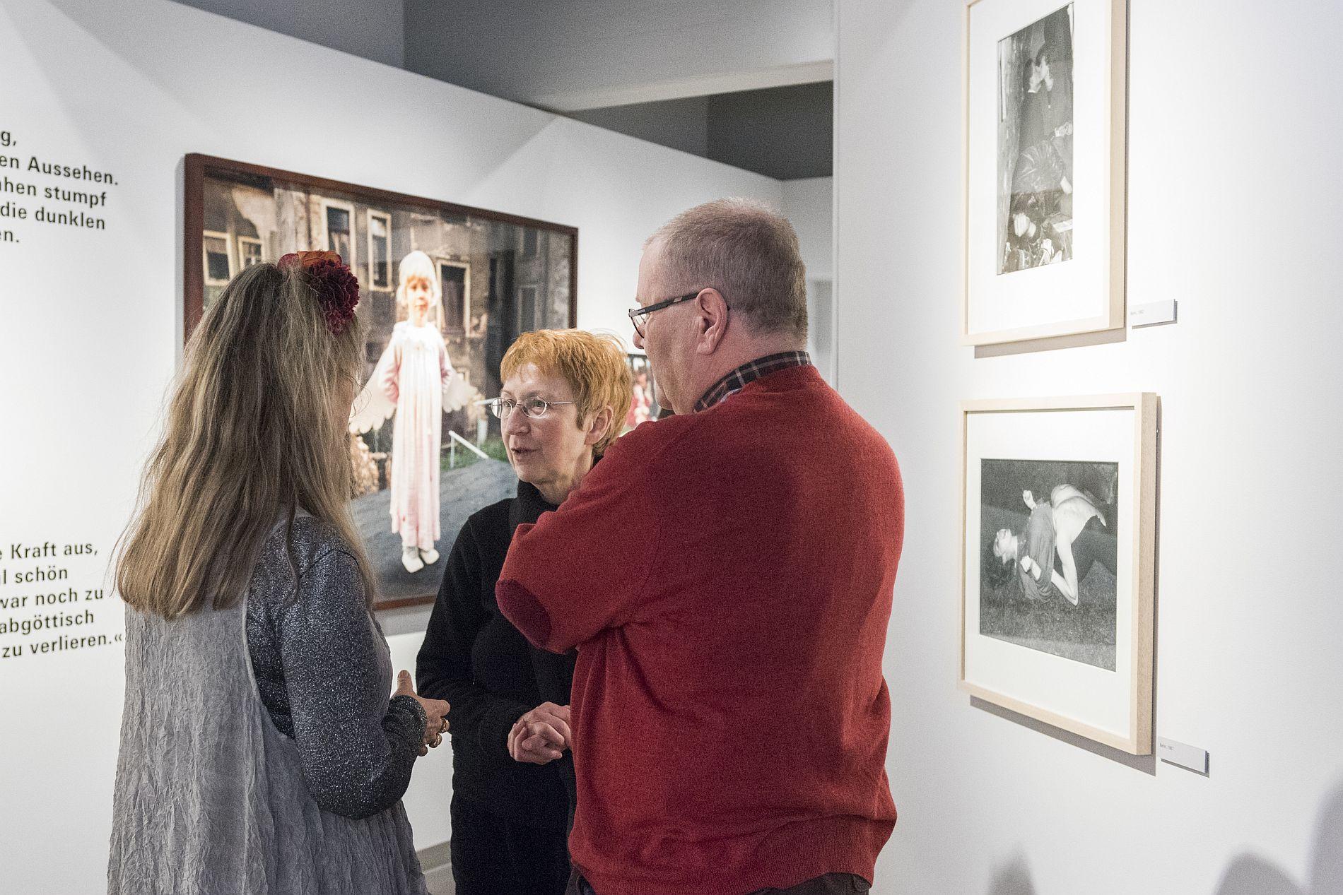 Gundula Schulze Eldowy spricht mit zwei Besuchern bei der Ausstellungseröffnung im Ausstellungspavillon Bonn