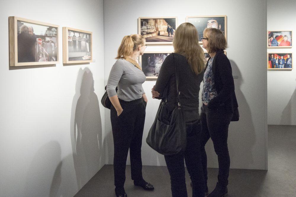 Drei junge Frauen betrachten gerahmte Fotografin an einer Zwischenwand, weitere Bilder hängen um sie herum