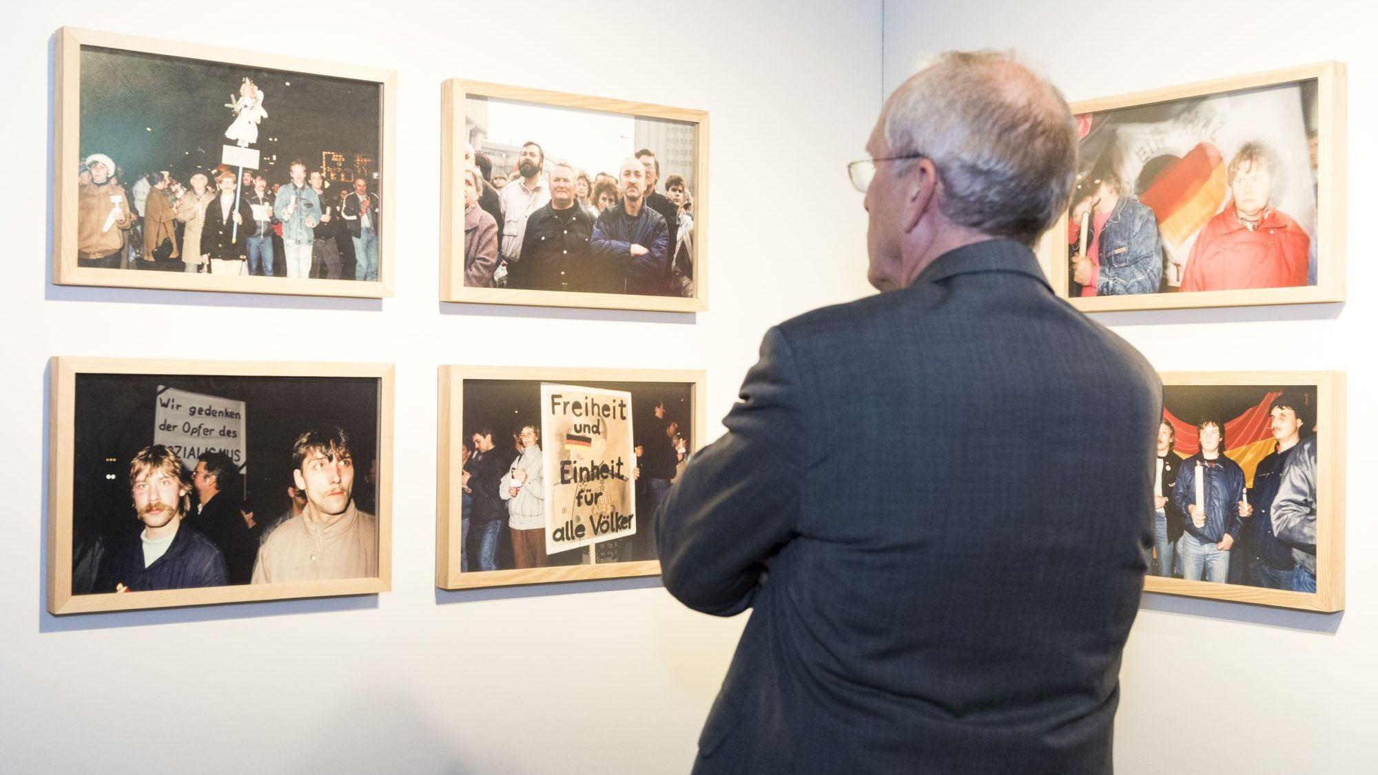 Ein älterer Mann steht mit dem Rücken zur Kamera und betrachtet sechs gerahmte Fotografien an einer Wand