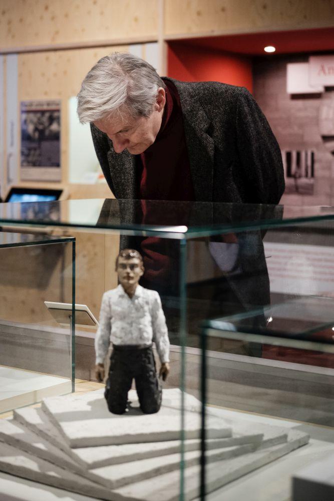 """Mann beugt sich über Modell """"Kniender Riesenmann"""", einen Entwurf zum Einheitsdenkmal"""