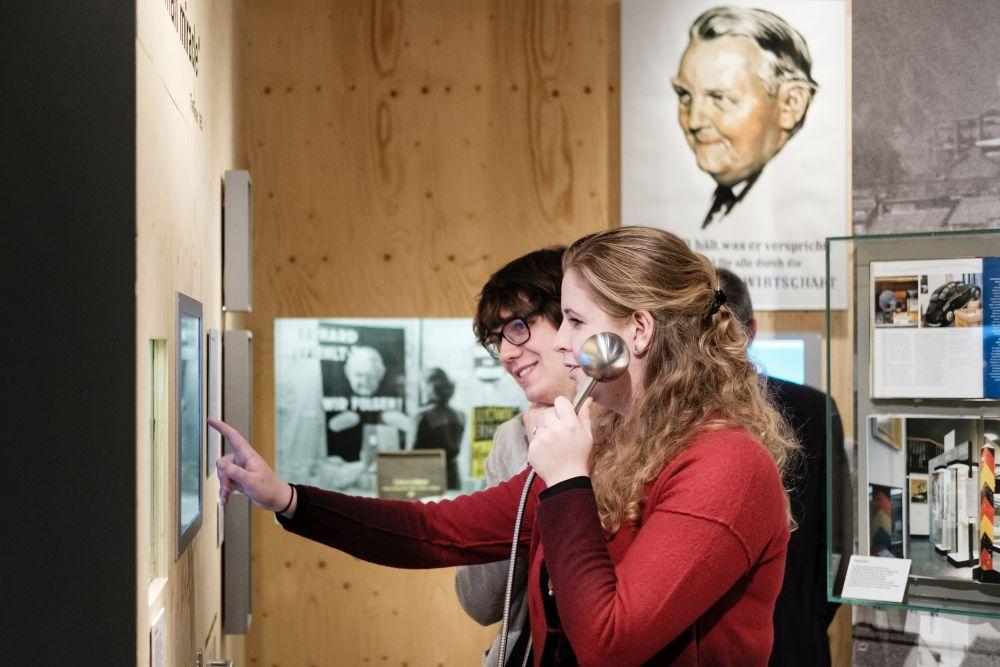 Junge Menschen an einer Hörstation zum Wirtschaftswunder