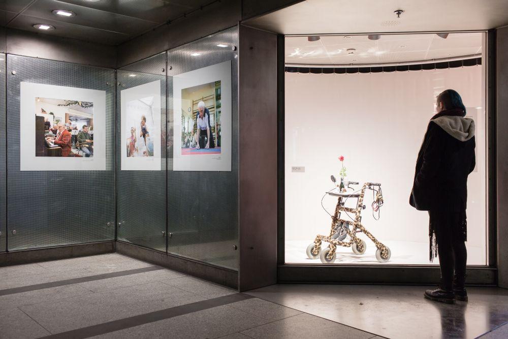 Eine junge Frau steht in einer U-Bahn-Station vor einem großen Schaukasten mit einem Rollator, der mit Tigerfellstoff umwickelt ist. Links neben dem Schaukasten hängen drei große Fotografien in großen Passepartouts