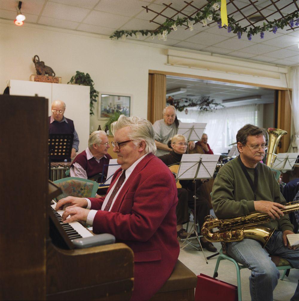 Ein älterer Mann sitzt in einem Zimmer am Klavier, hinter ihm weitere Senioren mit Instrumenten und Notenständern
