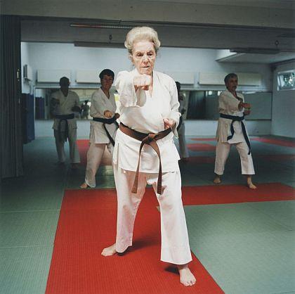 Das Foto zeigt eine Seniorin im Karate-Anzug beim Karate-Training