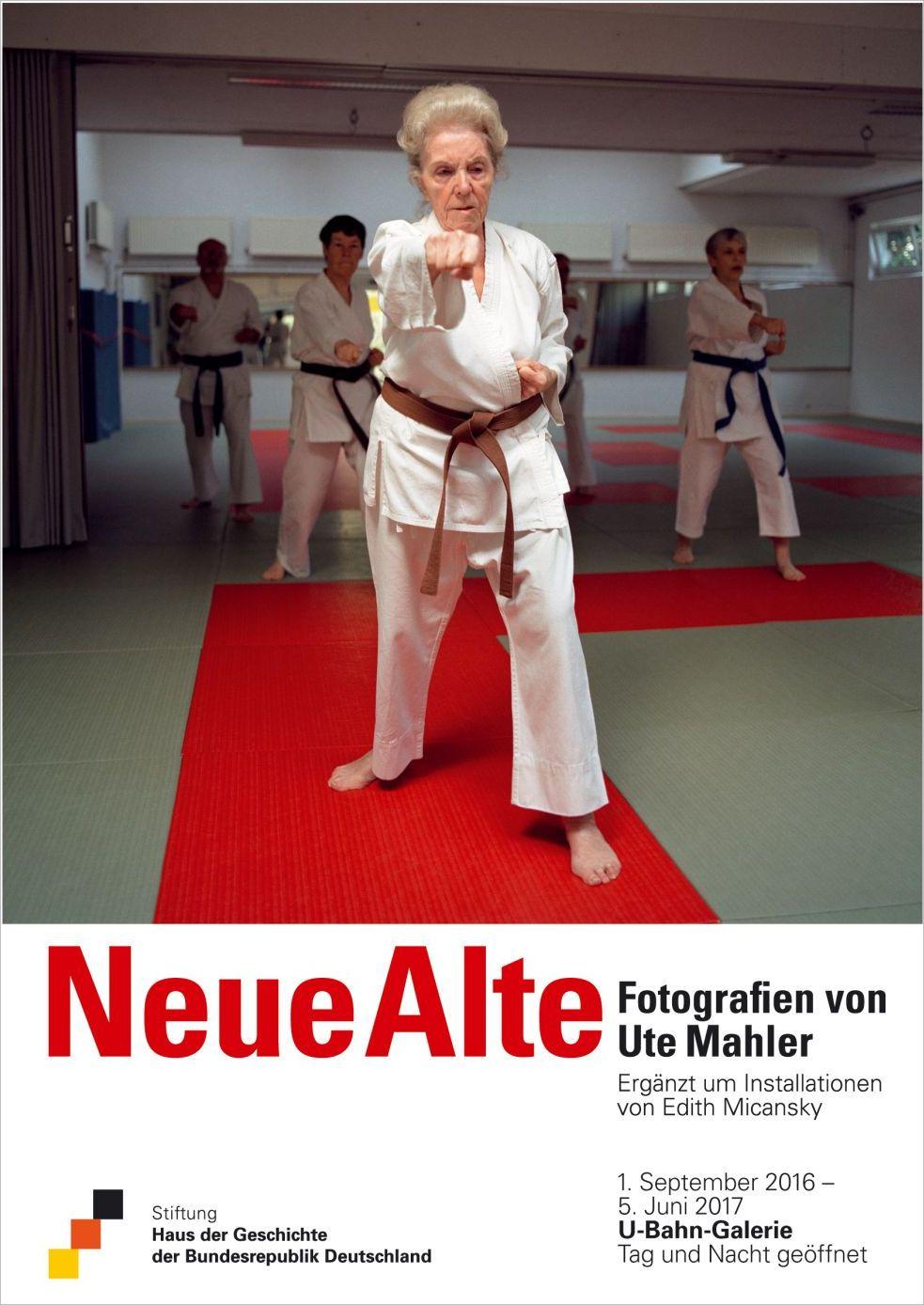 Eine alte Frau steht im weißen Karateanzug in einem großen Raum auf einer roten Matte, um die Hüfte hat sie einen braunen Textilgürtel geknotet. Hinter ihr drei weitere Menschen in gleicher Kleidung und Position