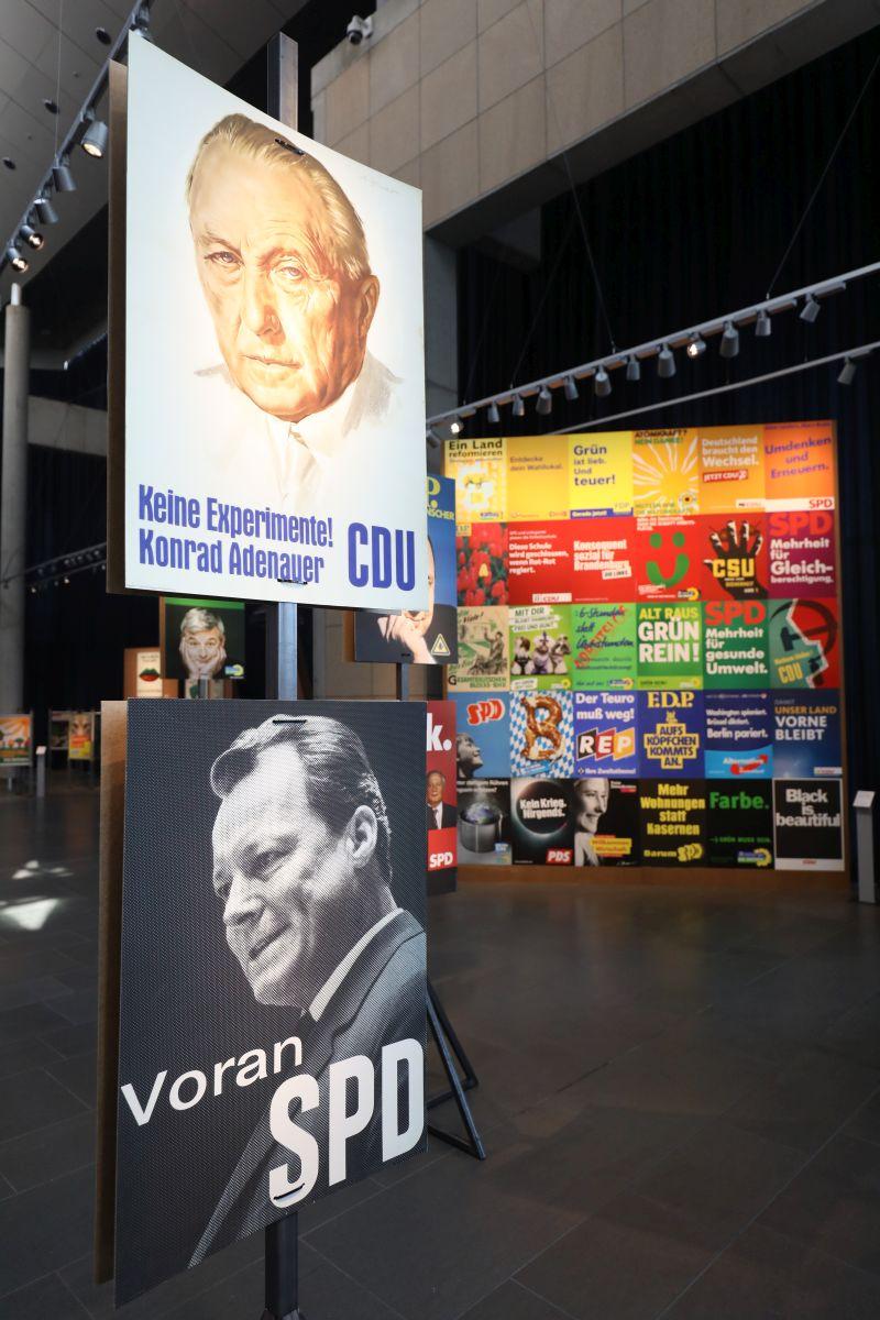 Das berühmte CDU-Plakat mit Konrad Adenauer und dem Slogan Keine Experimente sowie Willy Brandt und der Slogan Voran SPD im Vordergrund und eine große Wand mit vielen weiteren Plakaten im Hintergrund.