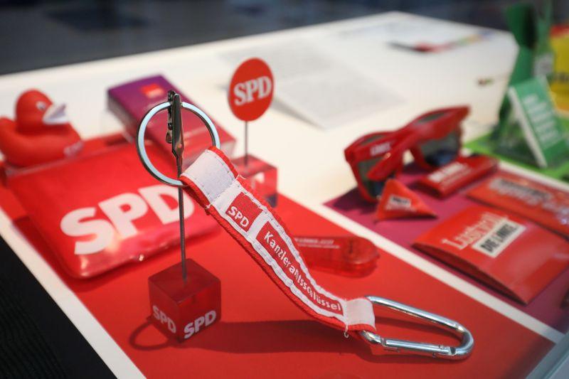 Ein Schlüsselanhänger, eine Sonnenbrille, eine Quietscheente und weitere Gegenstände mit den Logos von SPD und Die Linke.