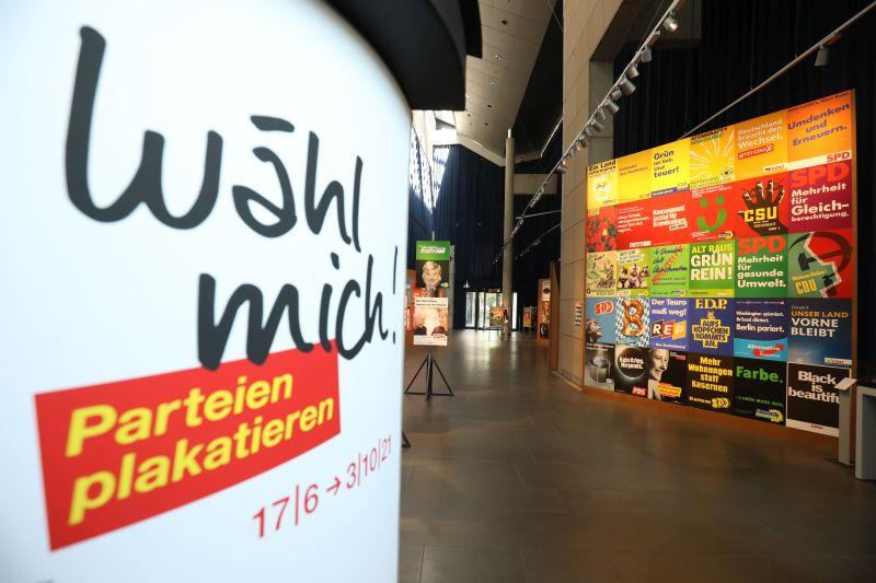 Blick in die Ausstellung mit dem Ausstellungspalakt und einer farbigen Wand mit diversen Wahlplakaten