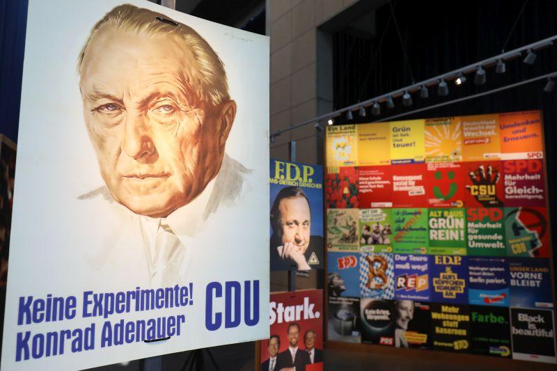 Das berühmte CDU-Plakat mit Konrad Adenauer und dem Slogan Keine Experimente und eine große Wand mit vielen weiteren Plakaten im Hintergrund.