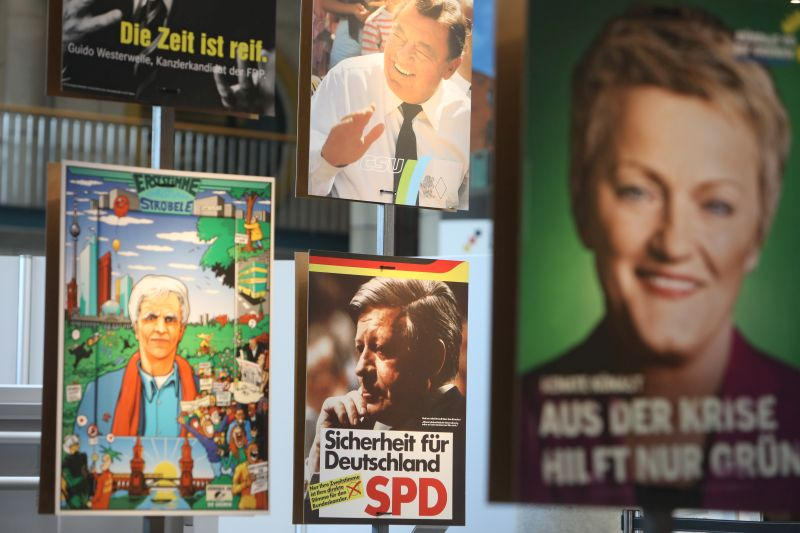 PersonalHans-Christian Ströbele, Hans Josef Strauß, Helmut Schmidt und Renate Künast werben auf Wahlplakaten für ihre Parteien.