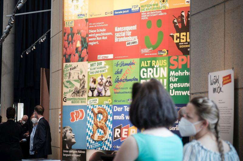 Zwei Frauen vor einer bunten Wand aus nach Farbe angeordneten Wahlplakaten.