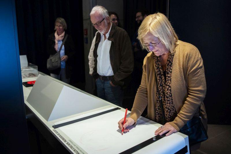 Eine Besucherin zeichnet in der Ausstellung eine Karikatur auf ein großes Blatt Papier.