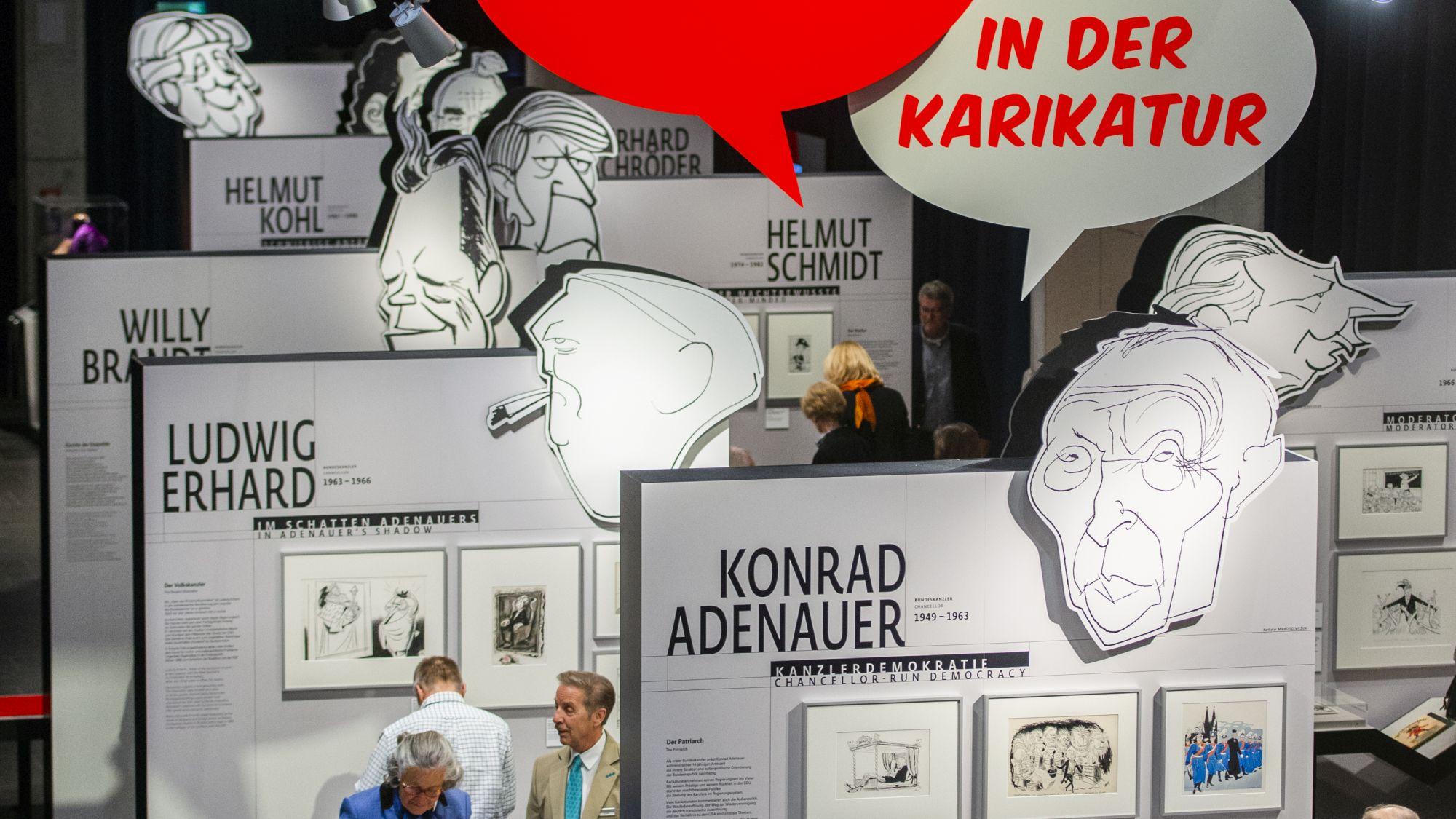 Vogelperspektive auf die Ausstellung mit großen Karikaturen der deutschen Bundeskanzler.