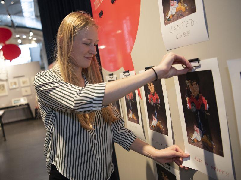 Eine Besucherin hängt eine farbig ausgedruckte Karikatur an eine Ausstellungswand.