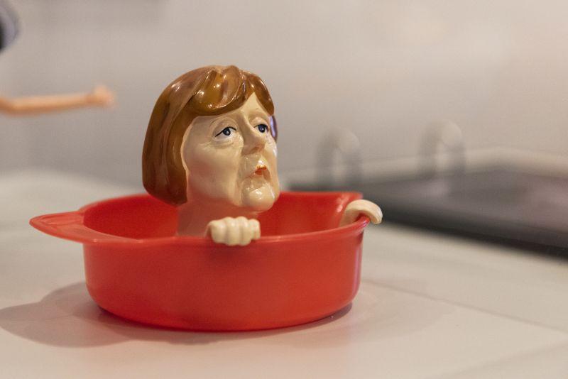 Eine Zitronenpresse aus Plastik, bei der die Zitrone auf dem Kopf von Angela Merkel ausgedrückt wird.