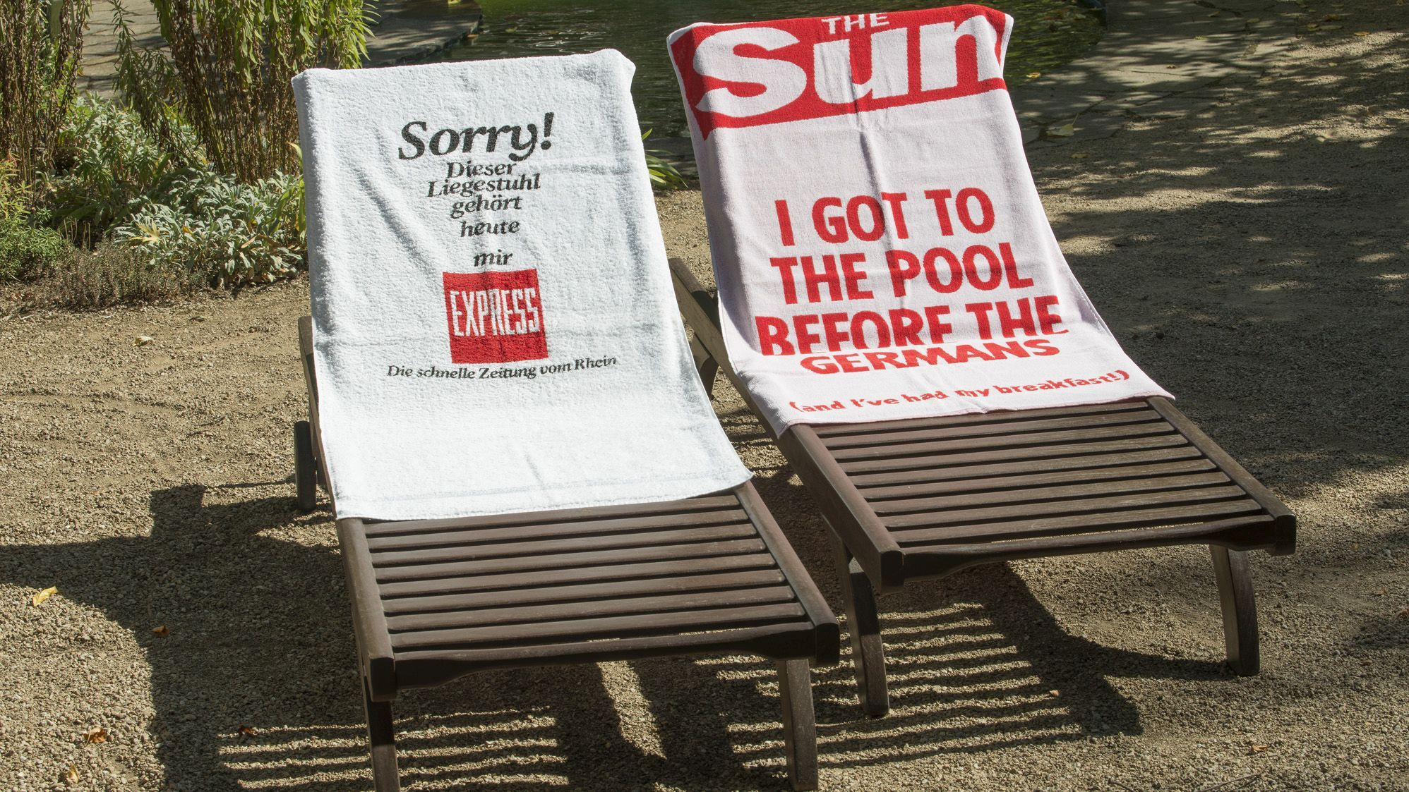"Two deck chairs with towels, one by the German newspaper Express, ""Sorry, dieser Liegestuhl gehört heute mir!"" and one by the british newspaper ""The Sun"", ""I got to the pool before the Germans""."