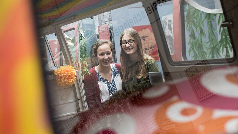 Zwei junge Mädchen stehen am VW Bulli in der Dauerausstellung im Haus der Geschichte in Bonn