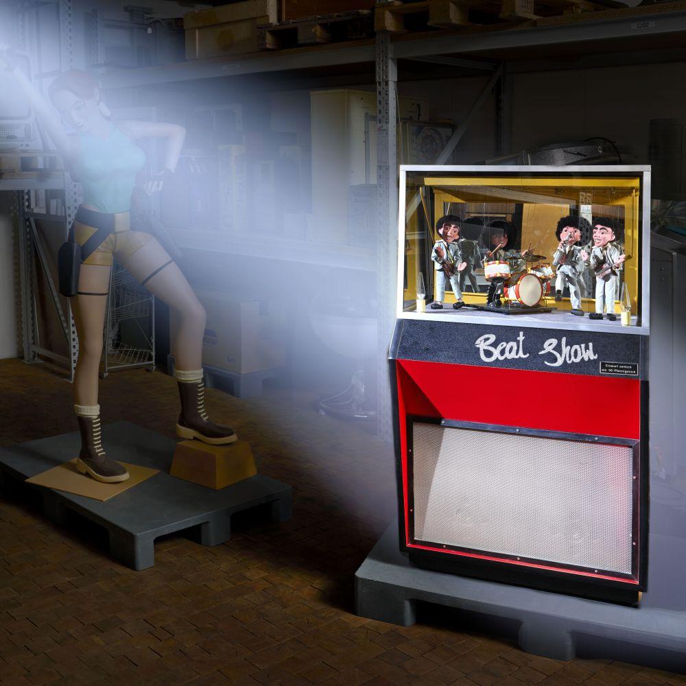 Angestrahlt im Vordergrund steht eine alte Musikbox mit vier Musiker-Marionetten und der Aufschrift Beat Box, dahinter im Halbdunkel eine lebensgroße Lara Croft-Figur und vollgestellte Regale.