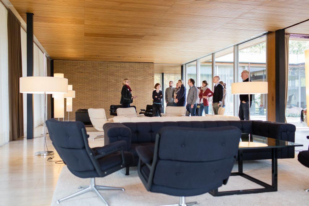 Ein länglicher Raum, an den beiden Seitenwänden Glas, eine dunkle und eine helle Sitzgarnitur, eine Besuchergruppe