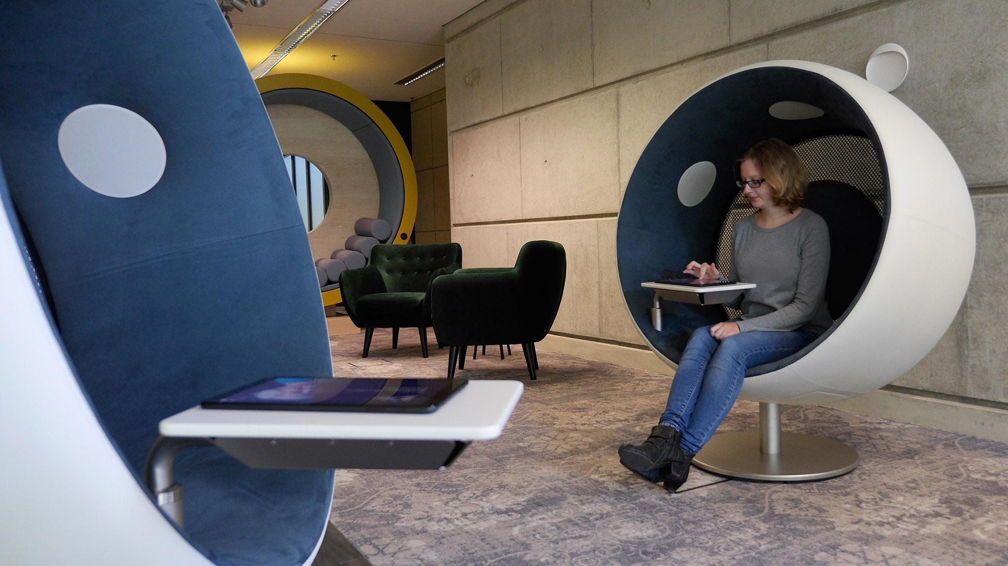 Eine Besucherin sitzt in einem Sessel mit einem Tablet in der Lounge