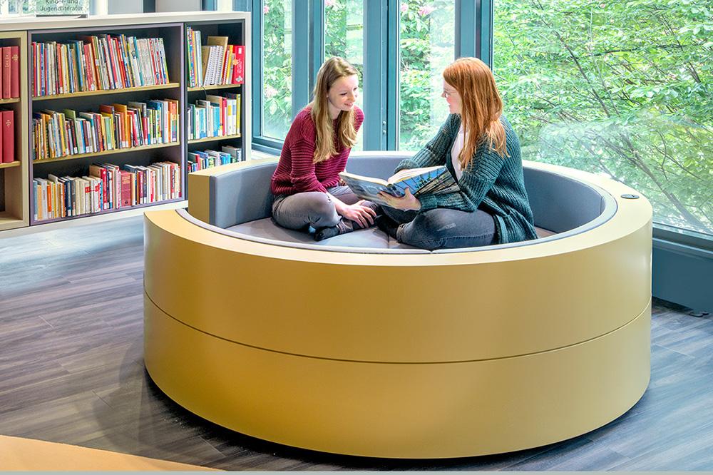 Zwei junge Frauen sitzen auf einem Sofa in der Bibliothek, dahinter steht ein Bücherregal.