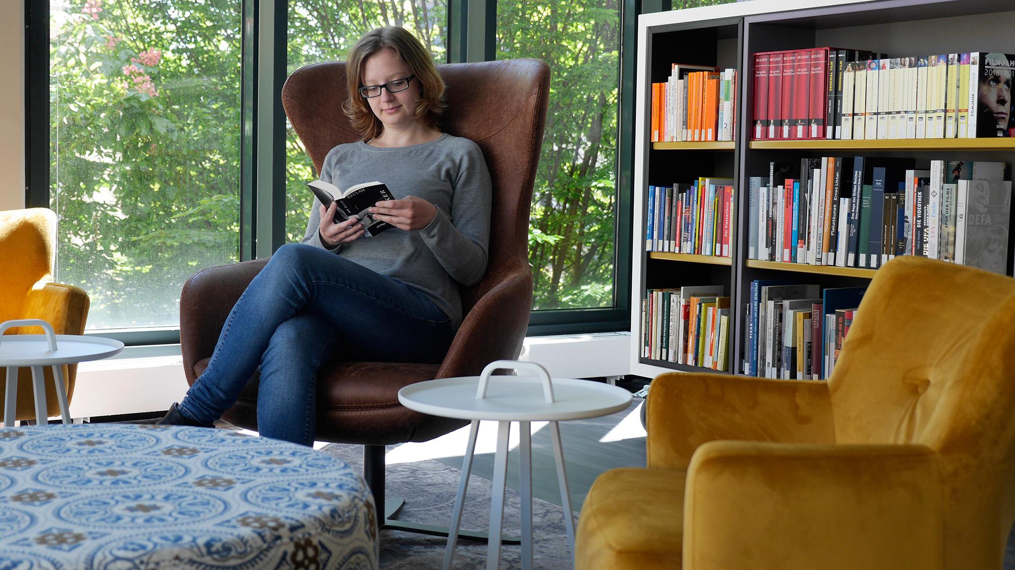 Eine Besucherin sitzt im Sessel mit einem Buch in der Lounge