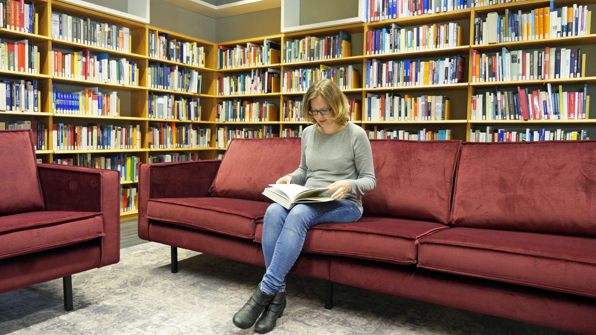 Eine Besucherin sitzt auf einem gemütlichen Sofa und liest