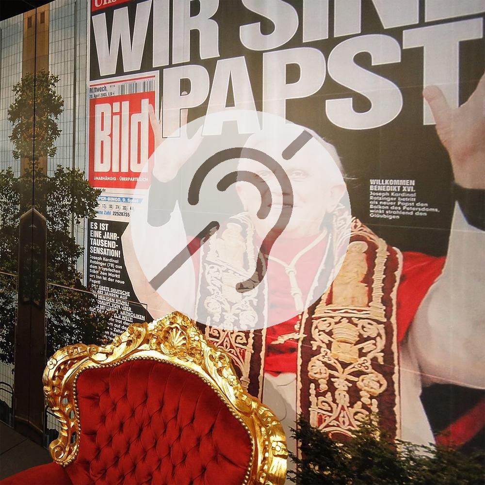 """Papststuhl in der Ausstellung """"Deutsche Mythen seit 1945"""" mit Symbol für Hörbeeinträchtigung"""