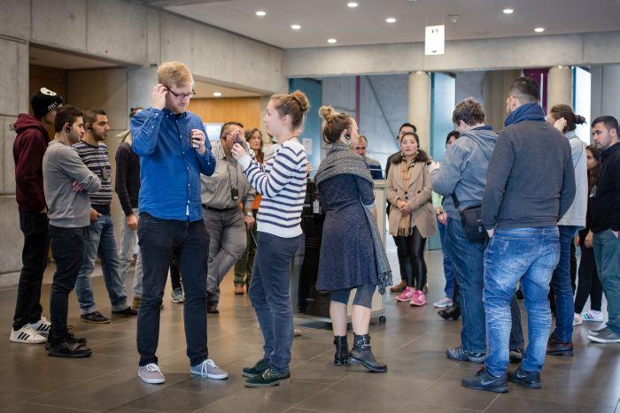 Besucher legen Kopfhörer im Foyer an