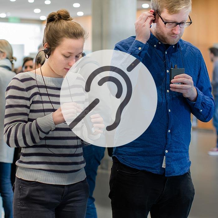 Besucher mit Kopfhörern und Empfangsgeräten