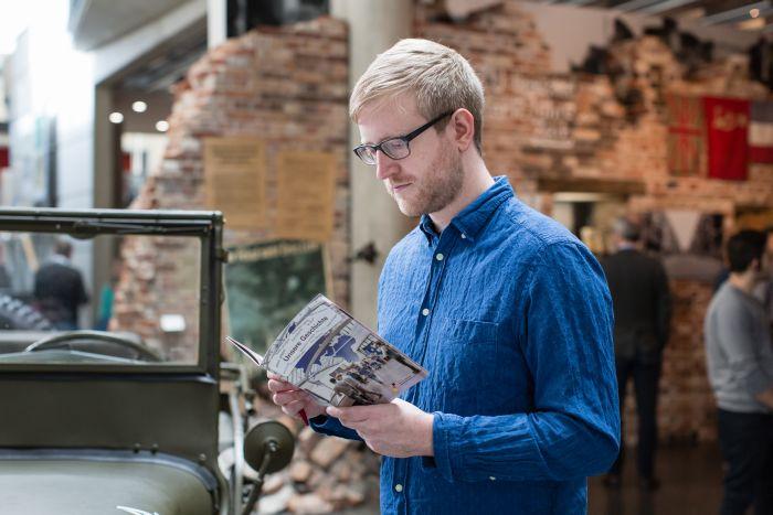 Ein Besucher liest im Heft 'Unsere Geschichte'