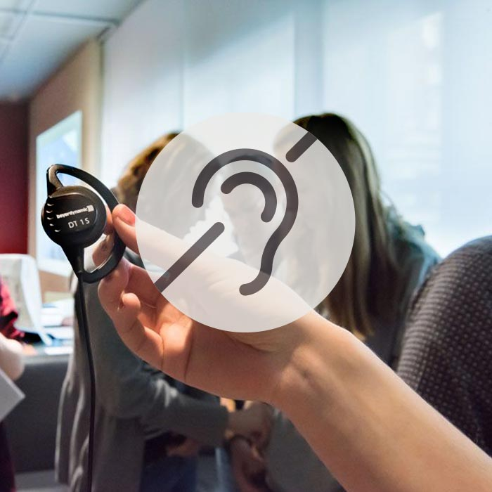 Ein Besucher hält einen Kopfhörer des Gruppenführungssystems