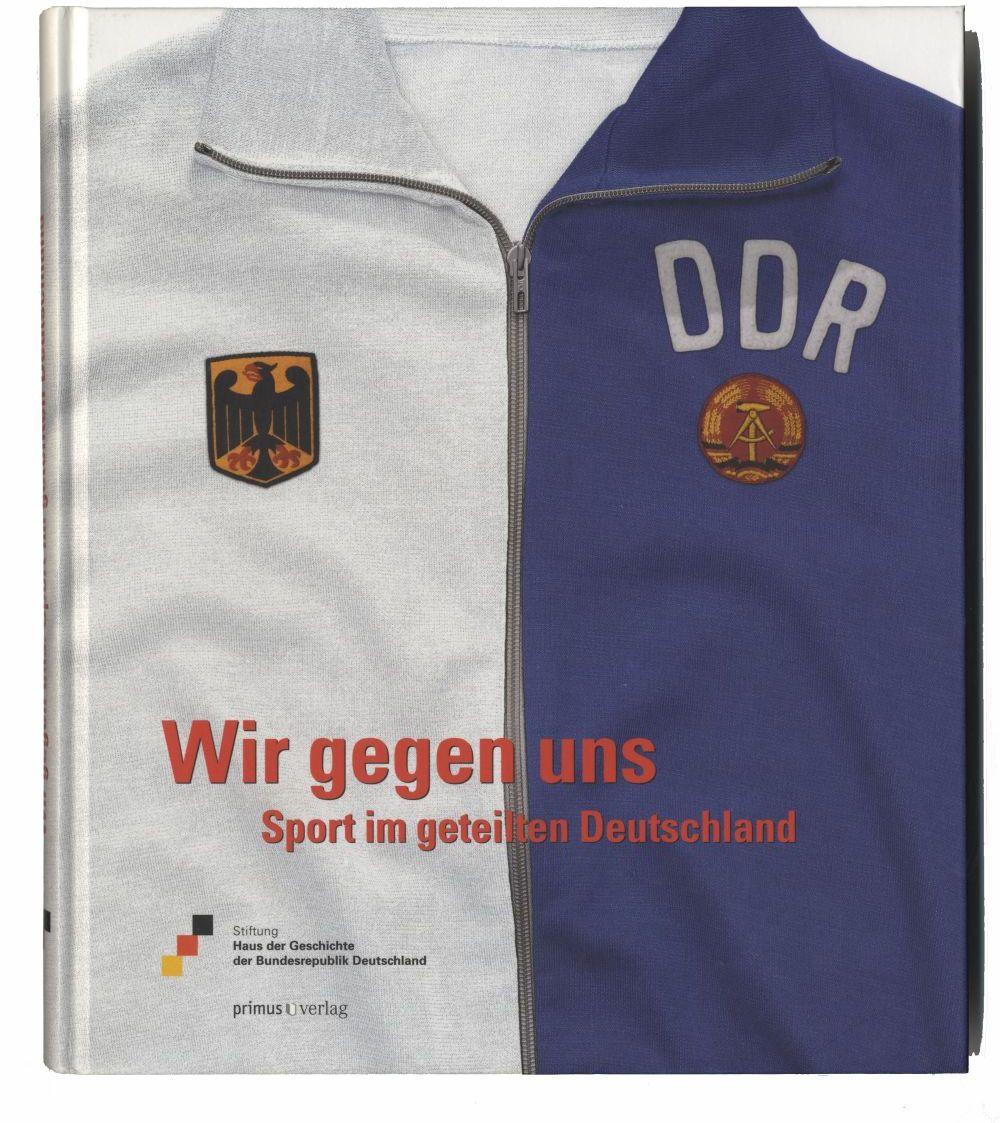 Buch zur Ausstellung mit einer Sportjacke auf dem Cover, die auf der einen Seite des Reißverschlusses weiß ist mit Bundesrepublik-Wappen, auf der anderen Seite blau mit DDR-Wappen