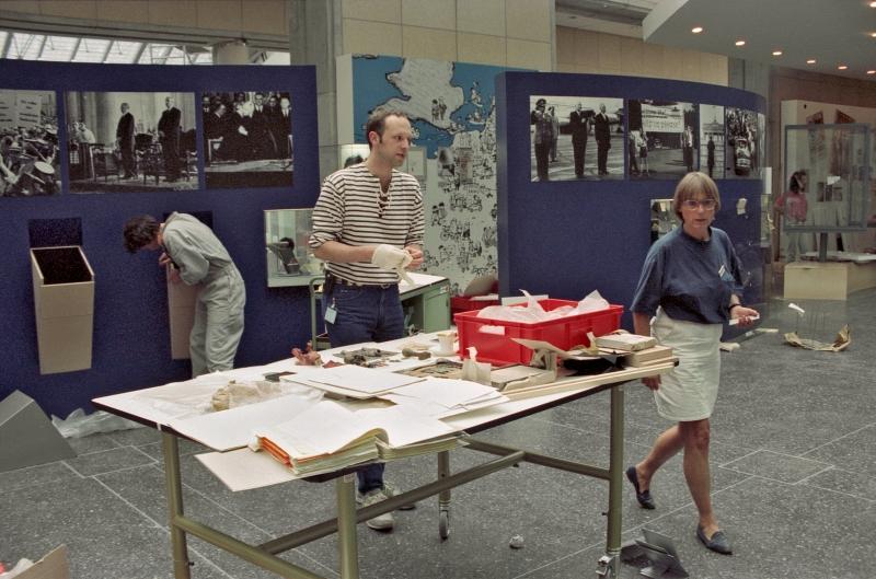 Zwei Personen arbeiten an einem Tisch mit Ordner und Ausstellungsobjekten, eine dritte schraubt an der Ausstellungsarchitektur