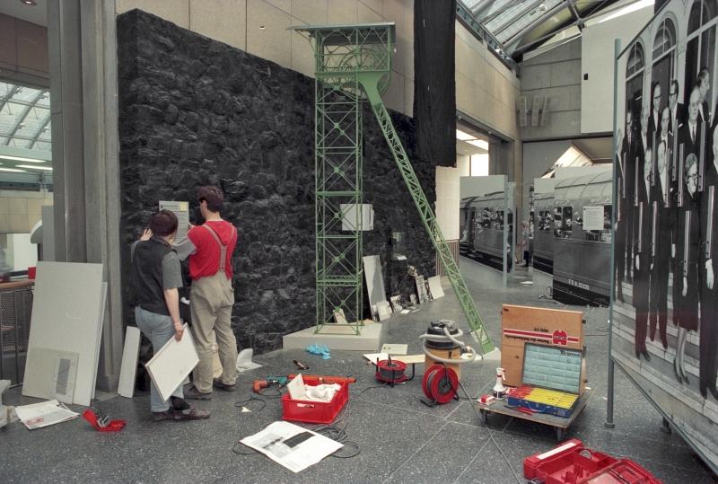 Zwei Arbeiter in der Ausstellung mit schwarzer Wand und Förderturm