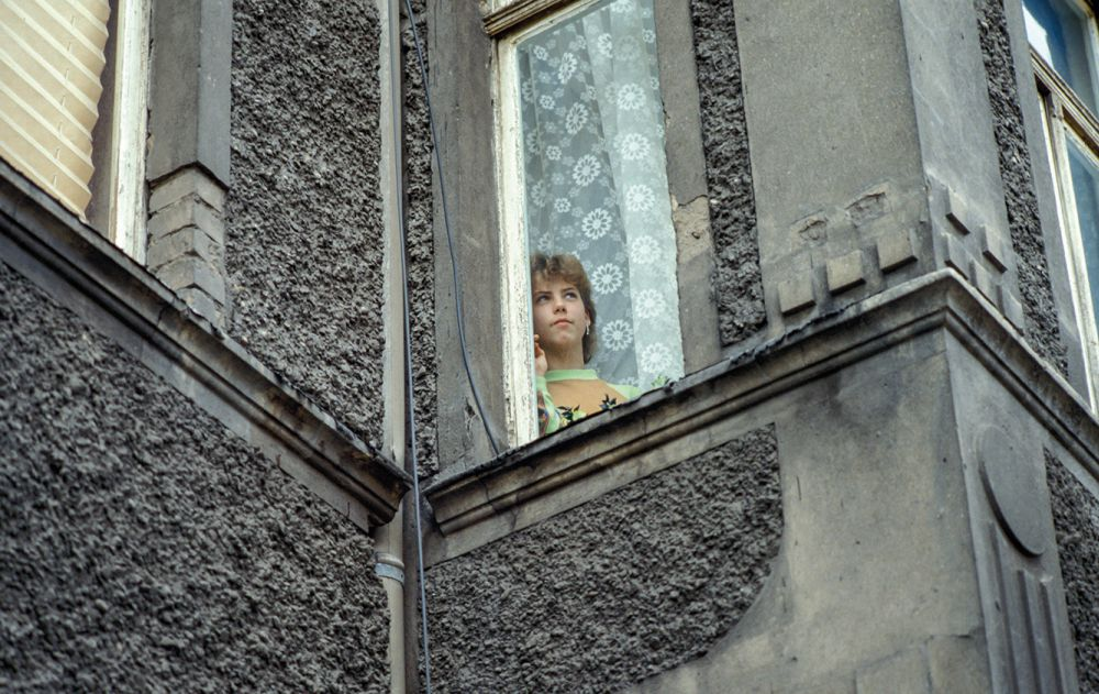 Young woman looks out of the window