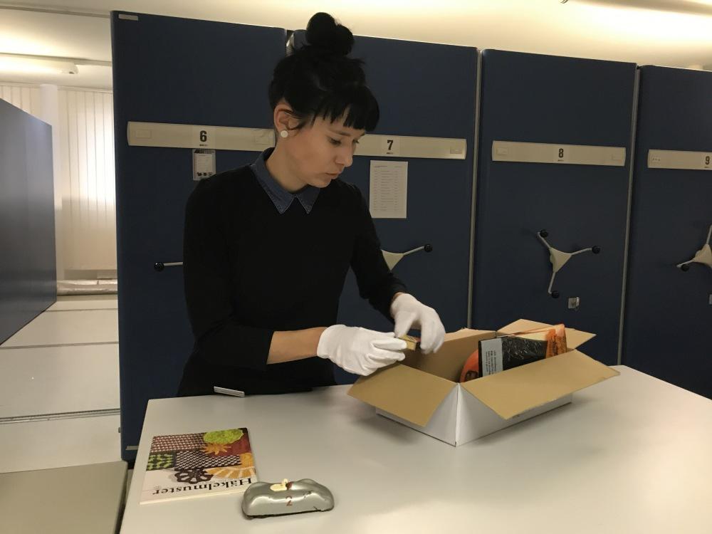 Marie Mohnhaupt packt die Objekte aus