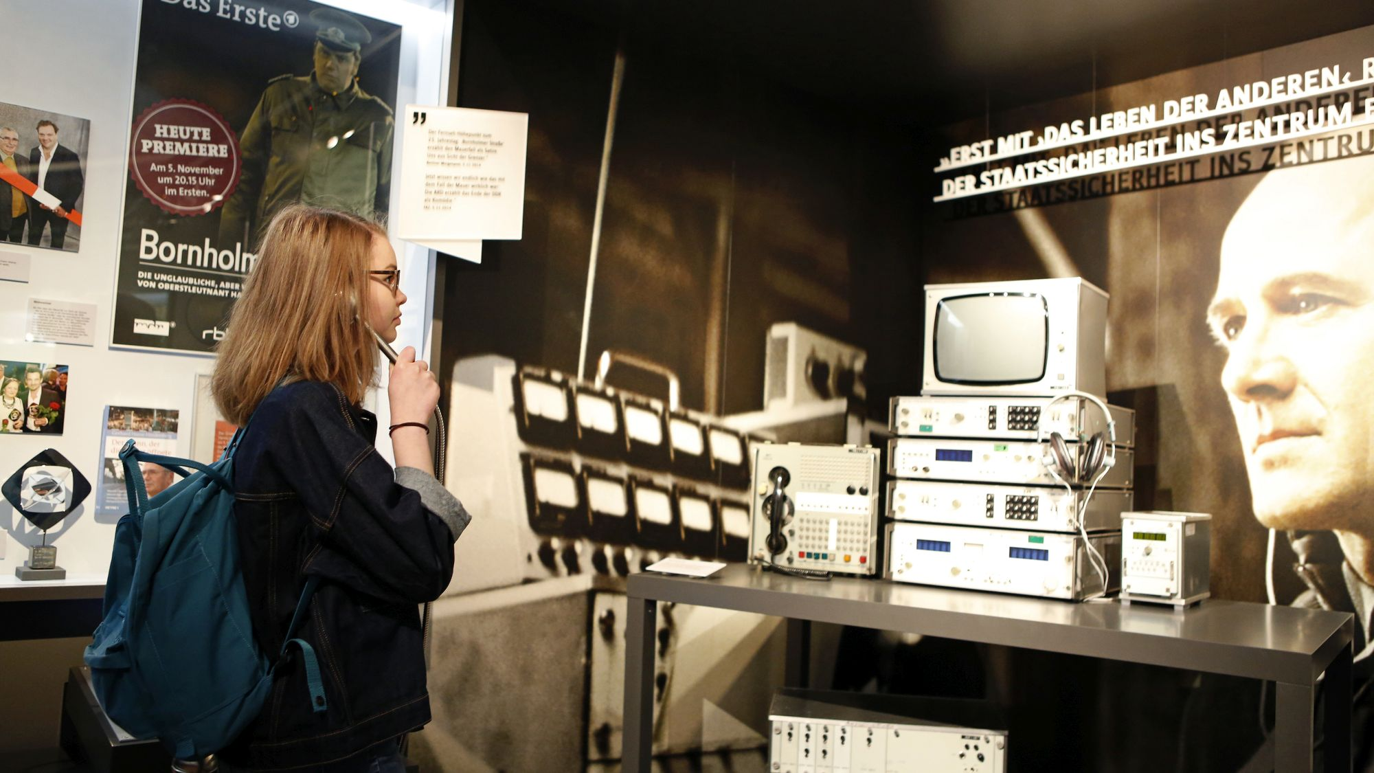 A young woman listens at a media station in the exhibition