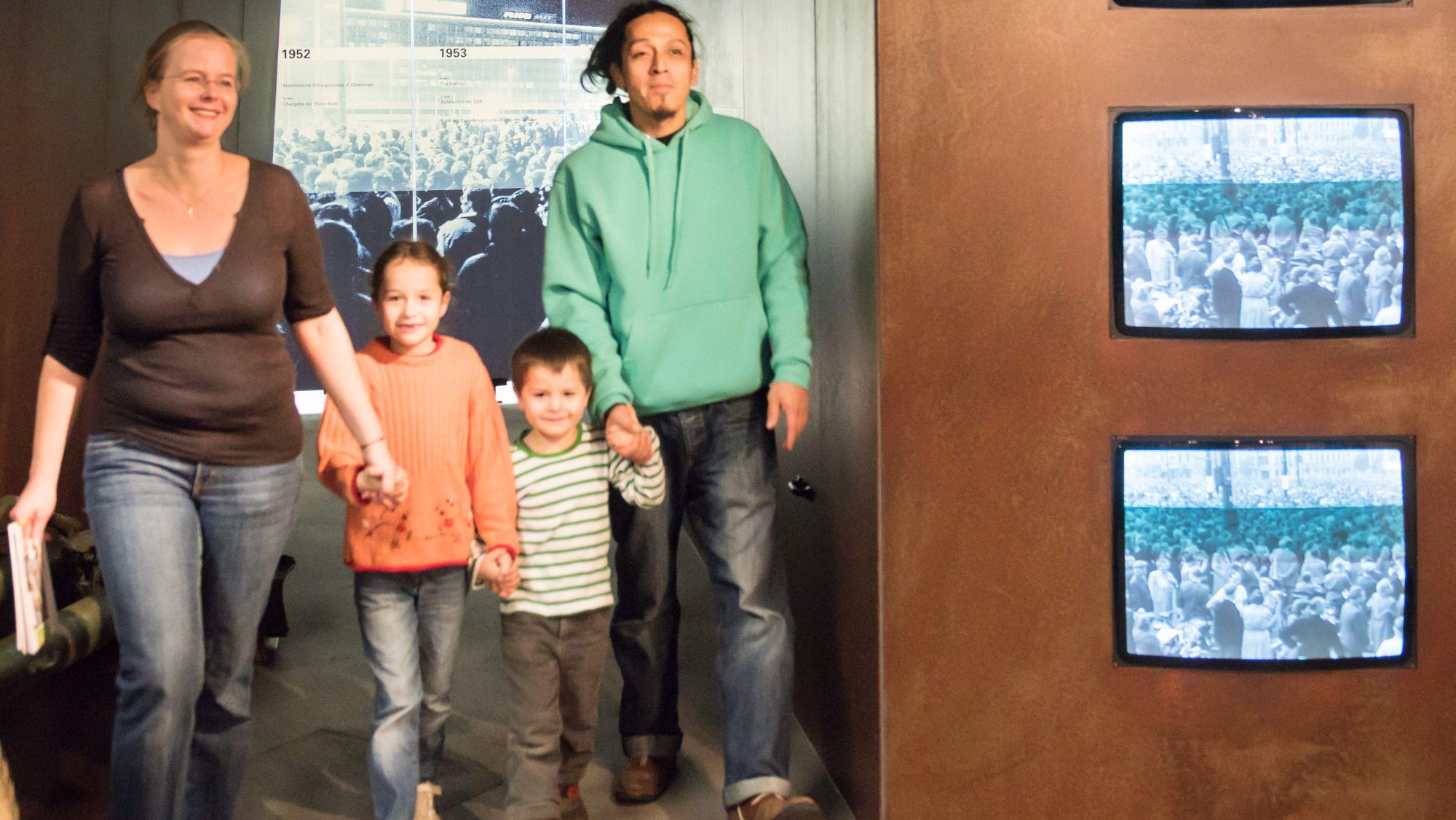 Eine Familie fasst sich an den Händen, links die Mutter, neben ihr ein etwa achtjähriges Mädchen, ein etwa fünfjähriger Junge und ganz rechts der Vater