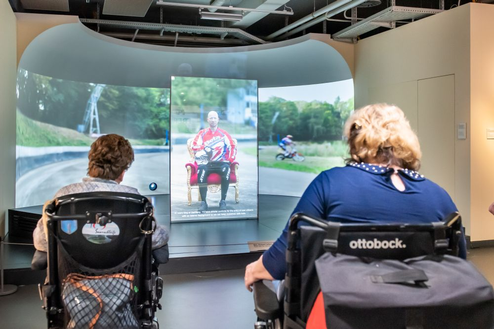 Wheelchair users in front of the installation of photographer Bettina Flitner