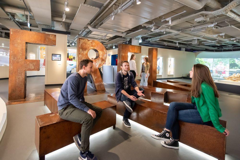 Besucherinnen und Besucher diskutieren in der Dauerausstellung